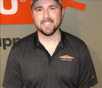 Male with brown hair and a mustache and beard. Wearing a SERVPRO cap and gray polo.