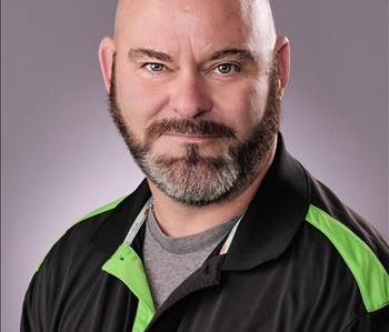 Male with buzzed dark hair and a mustache and beard. Wearing a black and green polo.